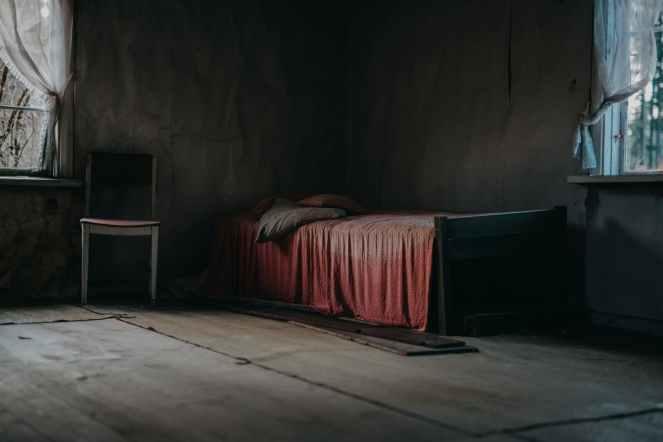 wooden bed beside window